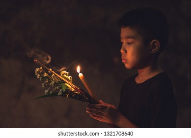 Asian young boy buddhist ceremony walk with lotus, white flowers, incense and candle in hand around temple at the night time.Paying respect to Buddha.Believe in the religion concept.