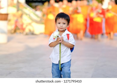 Asian young boy holding lotus walk with lighted candles in hand around a temple with a group of monk background.