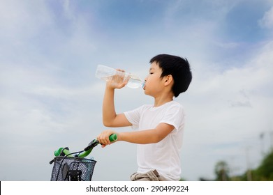 Asian young boy sit on bicycle  drinking fresh water from plastic bottle after sport in daylight