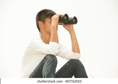 Asian young boy sit is seeking binoculars .