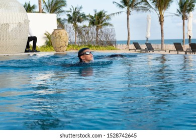 Asian young boy swimming breaststroke in a swimming pool