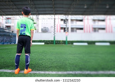 Asian young boy waiting to come in at the junior football training.Children playing soccer on the beautiful turf sport field in practicing day.Sports,Athlete,People,Health Care Concept.