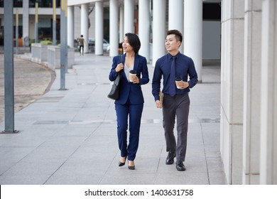 Asian young business partners walking in the city together talking and drinking coffee from disposable cups
