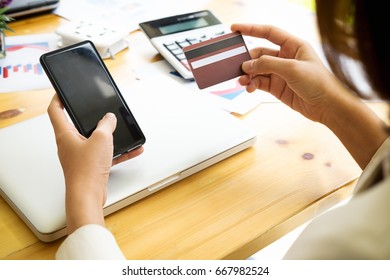 asian young business woman hands holding credit card and using laptop smart phone Online shopping.Online shopping concept