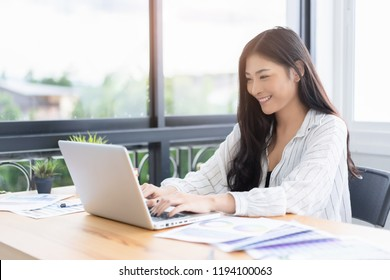 Asian young business women working with new project modern loft,laptop in coffee shop cafe, Analyze plans, papers, hands texting keyboard.Generic design notebook,technology or startup business concept