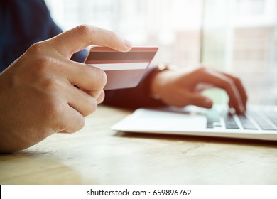 asian young businessman hands holding credit card and using laptop smart phone Online shopping.Online shopping concept