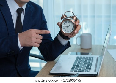 Asian young businessman on the blue suit man working against time on the desk. On the desk are the alarm clock, calculator and business document. He pointing his finger to the clock.