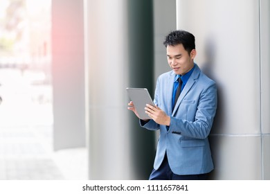 Asian young businessman using tablet update modern life in morning