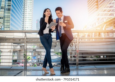 Asian Young businesswoman explaining report to her boss at meeting outdoor