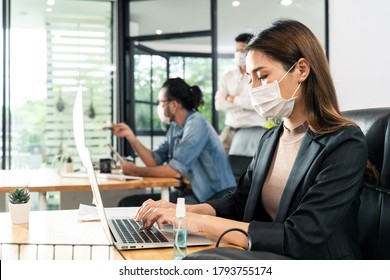 Asian young businesswoman working on computer in office with new normal lifestyle concept. Man and woman wear protective face mask and keep distancing to prevent covid virus after company reopen again