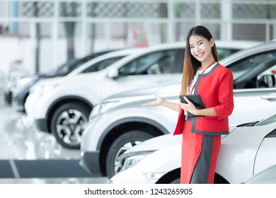 Asian young car saleswoman holding calculator with a welcome display in showroom, Car dealer woman. Auto dealership and rental concept background.