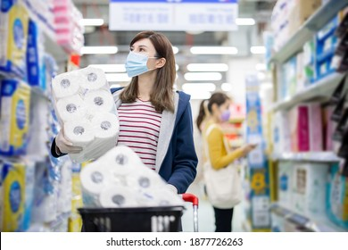 asian young career woman or homemaker walk in aisle and pick up paper towels at grocery store with face mask during virus epidemic outbreak