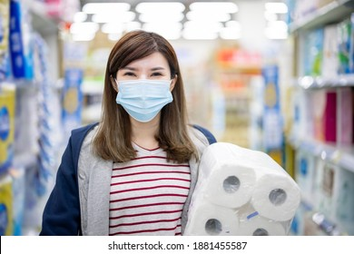 asian young career woman or homemaker walk in aisle and pick up paper towels at grocery store with face mask during virus epidemic outbreak - she look to you