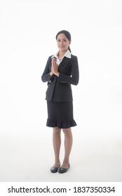 Asiatische junge selbstbewusste und erfolgreiche Geschäftsfrau, die mit thailändischer Kultur auf einzeln weißem Hintergrund grüßt und respektvoll reagiert