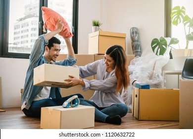 Asian young couple carrying big cardboard box for moving in new home, Helping relocate and joshing together, Moving and House Hunting concept, selective focus