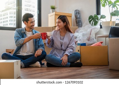 Asian young couple are clinking coffee cups after successfull packing the big cardboard box for moving in new home, Moving and House Hunting concept,