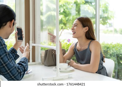 Asian young couple eating out together at new normal social distance restaurant with table shiled partition reduce infection of coronavirus covid-19 pandemic. Restaurant new normal lifestyle.