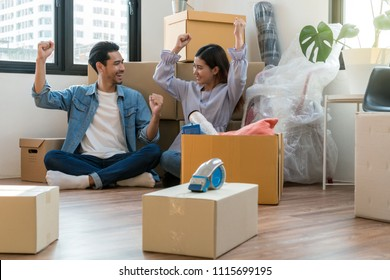 Asian young couple are glad after successfull packing the big cardboard box for moving in new home, Moving and House Hunting concept,