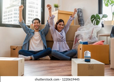 Asian young couple are glad after successfull packing the big cardboard box for moving in new place, Moving and House Hunting concept,