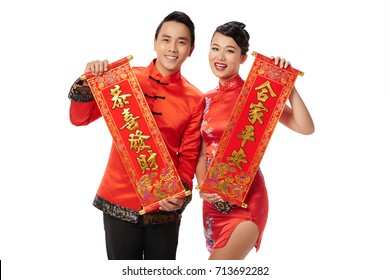 Asian young couple holding scrolls with New Year couplets