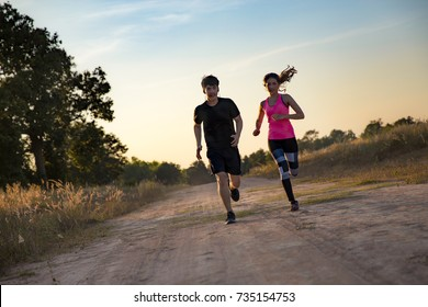 Asian Young couple running at forest trail.