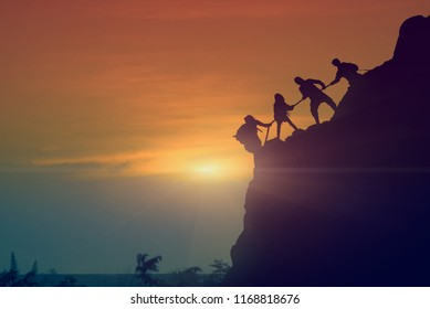 Asian young couple silhouette climbing the mountain hiking and teamwork concept, sunset background