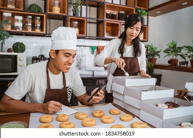 Asian young couple sitting when preparing of donuts order using smartphone to communicate with customers from the kitchen after making donuts together.