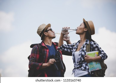 Asian young couple travelers to drink water on a green background, Hiking concept, Smiley face.