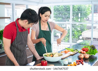 Asian young couple's in apron, make cooking together. Woman mix salad dressing with vegetable in big bowl. there are many components on counter, in kitchen, copy space.
