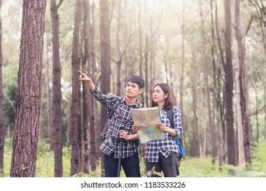 Asian young couples traveler with backpack looking map at sunny forest