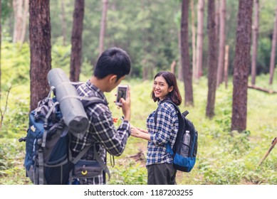 Asian young couples traveler with backpack take photo at forest, Travel and hiking concept