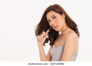 An Asian young cute girl pose with lipstick on white background