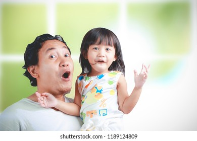 Asian young dad and his daughter have fun, while being carried in his father's arms, happy family