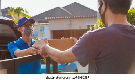 Asiatischer Junglieferant-Kurier mit Paketpost in Uniform die Schutzmaske Maske, die er erbringt und den Kunden, der die Vorderhaus unter curwenige Quarantäne-Pandemie-Koronavirus COVID-19