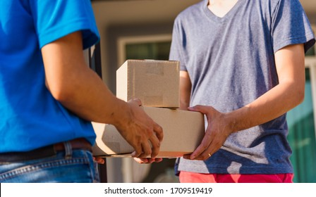 Asian Young delivery man courier with package post box in uniform he protective face mask he making service and customer receiving front house under curfew quarantine pandemic coronavirus COVID-19
