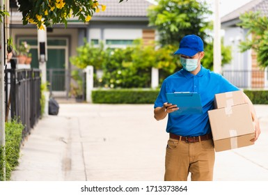 Asian young delivery man courier hold parcel post boxes he protective face mask service and walk looking for customer home location, under curfew pandemic coronavirus COVID-19