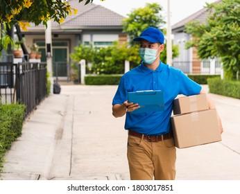 Asiatischer Junglieferant-Kurier hält Paketpostfächer für die Schutzmaske und geht zu Fuß nach dem Wohnort des Kunden, unter kurzes pandemisches Koronavirus COVID-19