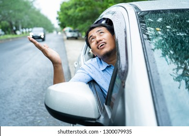 asian young driver opened the window and watched the sky will be rain because of cloudy