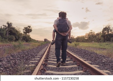Asian young father carrying his son on his back to travel by train during the summer holidays with sunset