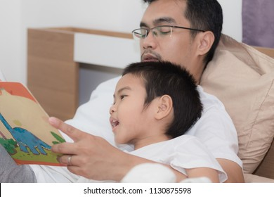 Asian young fathers read fable books to his son while lying in bed