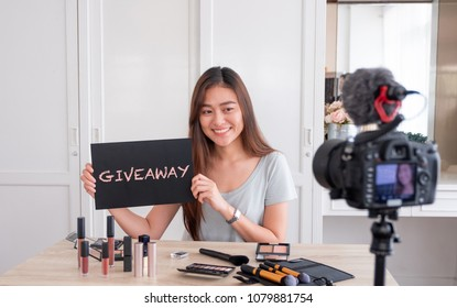 Asian young female blogger giveaway gift to fan following channel while recording vlog video with makeup cosmetic at home online influencer on social media concept.live streaming viral