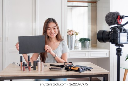 Asian young female blogger giveaway gift fan following channel while recording vlog video with makeup cosmetic at home online influencer concept.live streaming viral.mock up blackboard for your design