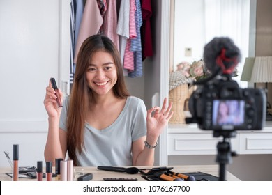 Asian young female blogger recording vlog video with makeup cosmetic at home online influencer on social media concept.live streaming viral