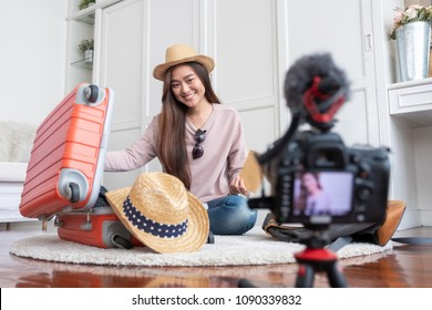 Asian young female blogger recording vlog video with vacation preparing to travel trip at home.online influcencer on social media concept.