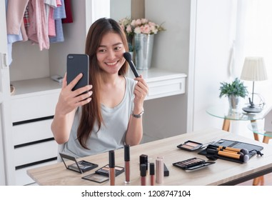 Asian young female blogger recording vlog video use mobile with makeup cosmetic at home online influencer on social media concept.live streaming viral