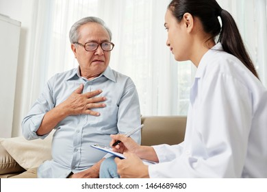 Asian young female doctor in white coat sitting listening to the senior patient and making notes in document during home visit