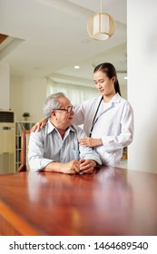 Asian young female doctor in white coat standing and talking to the senior man at the table during her home visit