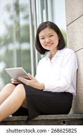 Asian young female executive holding a tablet