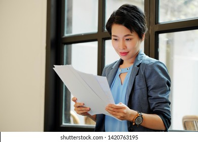 Asian young female executive reading a documents in her hands while working at office