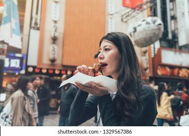 Asian young female model eating octopus ball dumpling on teeming dotonbori area osaka japan. local lady eating street food takoyaki with cheerful smiling face. huge puffer fish balloon in back